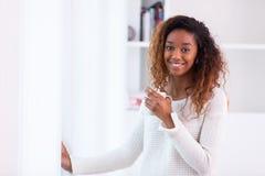 喝非裔美国人的妇女在她的客厅拿着cof 免版税库存图片