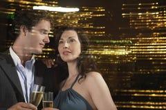 喝香宾的夫妇反对夜地平线 免版税库存照片