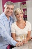 喝香宾的男人&妇女夫妇在厨房里 库存照片