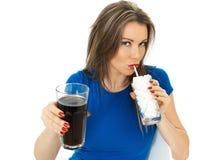 喝高糖泡沫腾涌的饮料的少妇 免版税图库摄影