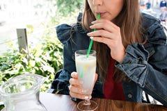 喝鲜美甜鸡尾酒,惊人的松弛天,鲜美柠檬水,室外大阳台的年轻微笑的女孩 图库摄影