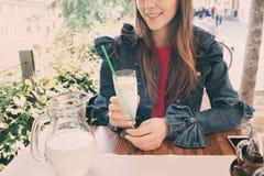 喝鲜美甜鸡尾酒,惊人的松弛天,鲜美柠檬水,室外大阳台的年轻微笑的女孩 库存照片