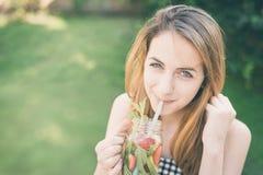 喝鲜美鸡尾酒的年轻微笑的女孩 免版税库存图片
