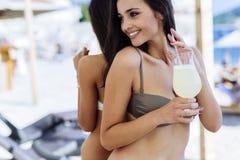 喝鸡尾酒的两个可爱的女孩 免版税库存照片