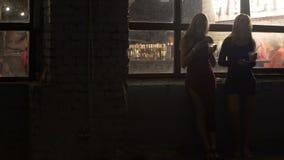 喝鸡尾酒的两名美丽的妇女,浏览在智能手机在夜总会 影视素材