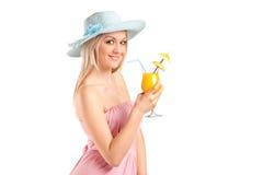 喝鸡尾酒的可爱的白肤金发的妇女 免版税库存照片
