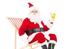 喝鸡尾酒的圣诞老人供以座位在太阳懒人 免版税库存图片