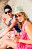 喝鸡尾酒的妇女在海滩 免版税库存照片