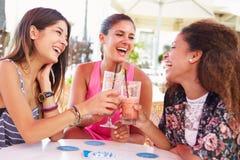 喝鸡尾酒的小组女性朋友在室外酒吧 免版税库存图片