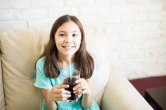 喝黑软饮料的美丽的女孩 库存照片