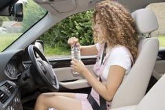 喝从一个瓶的年轻女性司机水 免版税库存图片