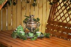 喝从俄国式茶炊的茶的全国俄国传统。 免版税库存照片