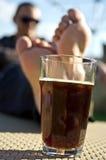 喝黑啤酒的人在庭院里 免版税库存照片