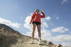 喝从在山的水瓶的女性慢跑者 免版税库存照片