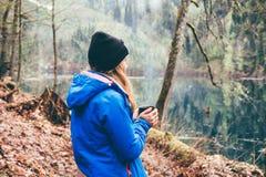 喝从在森林和山湖后面的一个杯子的旅行女孩 免版税库存照片