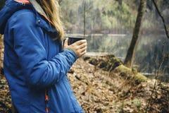 喝从在森林和山湖的一个杯子的旅行女孩 库存图片