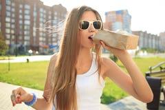 喝从在街道的一个纸袋的女孩 免版税库存图片