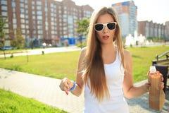 喝从在街道的一个纸袋的女孩 免版税图库摄影