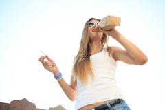 喝从在街道的一个纸袋的女孩 免版税库存照片