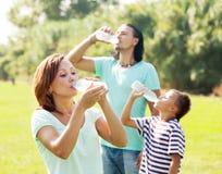 喝从塑料瓶的三口之家 免版税库存照片
