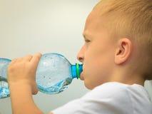 喝从塑料瓶的孩子纯净的水 免版税库存照片