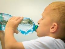 喝从塑料瓶的孩子纯净的水 免版税图库摄影