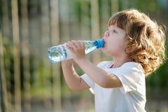 喝从塑料的小女孩净水 免版税库存照片