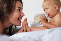 喝从有母亲微笑的瓶的婴孩 库存图片