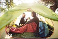 喝从杯子的游人微笑的夫妇咖啡在帐篷 免版税库存照片