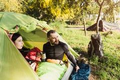 喝从杯子的游人微笑的夫妇咖啡在帐篷 库存照片