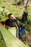 喝从杯子的男性游人咖啡在帐篷 免版税库存照片