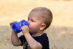 喝从杯子的婴孩 免版税图库摄影