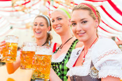 喝巴法力亚啤酒的朋友在慕尼黑啤酒节 图库摄影