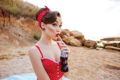 喝从玻璃瓶的妇女的年轻别针甜饮料 图库摄影