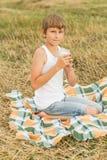 喝从玻璃的十几岁的男孩新鲜的原料乳 免版税库存照片