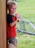 喝从水瓶的可爱的小孩男孩 免版税库存照片