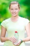喝从瓶的妇女冷的矿泉水在前的健身以后 免版税库存图片