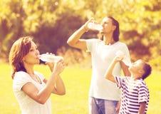 喝从瓶的普通的三口之家 免版税库存图片