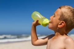 喝从水瓶的渴男孩 免版税库存图片