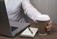 喝从纸杯的商人咖啡 免版税库存照片