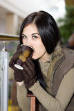 喝从纸杯的女孩热的茶在购物中心 免版税库存照片