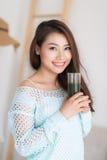 喝绿色新鲜蔬菜汁o的微笑的年轻亚裔妇女 免版税库存照片