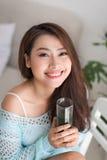 喝绿色新鲜蔬菜汁o的微笑的年轻亚裔妇女 库存照片