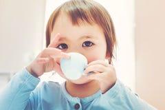 喝从茶杯的愉快的小孩女孩 库存图片