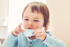 喝从茶杯的愉快的小孩女孩 库存照片