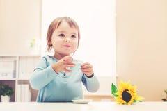 喝从茶杯的愉快的小孩女孩 免版税图库摄影