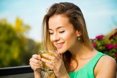喝绿茶的愉快的妇女户外 免版税图库摄影
