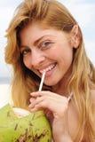 喝渴水妇女的海滩椰子 免版税库存图片