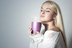 喝Coffee.Sweet女孩的美丽的白肤金发的妇女早晨 库存照片