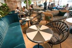 喝Eco友好的咖啡馆、长沙发和的人,吃食物 免版税库存照片